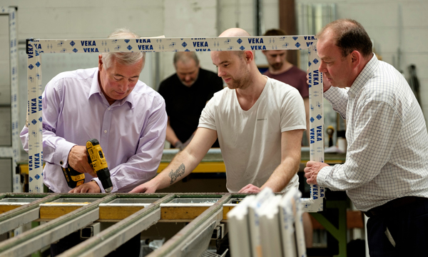 Sir Nigel Rudd tries his hand at finishing window frames with the Stevenswood team and Managing Director Ron Hepburn