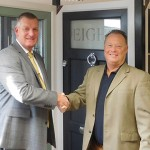 Earl Tate from Mila (left) congratulates Mark Hutchinson of Tradesmith on the company